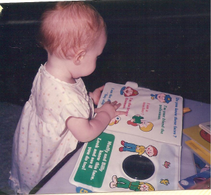 Bec reading to herself at 12 months
